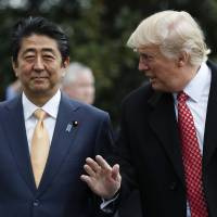 Prime Minister Shinzo Abe listens to U.S. President Donald Trump as they pause before boarding Marine One on the South Lawn of the White House in Washington, for the short trip to Andrews Air Force Base en route to West Palm Beach, Florida, on Feb. 10. | AP