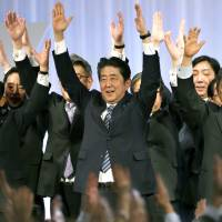 Prime Minister Shinzo Abe (center) shouts traditional banzai cheers with lawmakers and members of his ruling Liberal Democratic Party during its annual convention at a Tokyo hotel Sunday. | AP