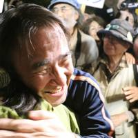 Hiroji Yamashiro, a prominent anti-U.S. base activist in Okinawa, hugs a supporter Saturday after being released on bail after five months of detention in Naha, Okinawa Prefecture. | KYODO