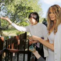 Japanese first lady Akie Abe and U.S. first lady Melania Trump feed koi at the Morikami Museum and Japanese Gardens in Florida on Feb. 11. | REUTERS