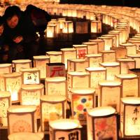 People look at lanterns placed at the municipal office building Saturday in Natori, Miyagi Prefecture, which was hit by the earthquake and tsunami disasters six years ago. The lanterns carried messages to encourage those affected by the disasters. | KYODO