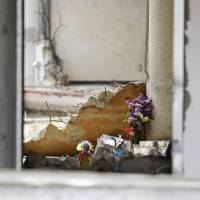 Flowers are placed in the Okawa Elementary School building in Ishinomaki, Miyagi Prefecture, on Saturday, the sixth anniversary of the March 11, 2011, earthquake, tsunami and nuclear disasters. The disasters claimed the lives of 84 students and staff at the school.   KYODO