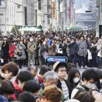 People observe a moment of silence in Tokyo's Ginza shopping district at 2:46 p.m. on Saturday, the time when a massive earthquake rocked the Tohoku region six years ago.   KYODO