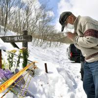 A man prays for victims of Monday's avalanche in Nasu, Tochigi Prefecture, at the entrance of the Nasuonsen Family Ski Resort on Wednesday. | KYODO