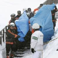 Firefighters rescue an avalanche victim at a ski resort in the town of Nasu, Tochigi Prefecture, on Monday morning. | KYODO
