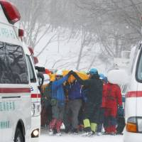Rescuers carry the injured to ambulances Monday after a group of high school students and teachers were hit by an avalanche in Nasu, Tochigi Prefecture, earlier in the day.   KYODO