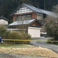 A police officer stands near tape Saturday blocking off a deserted home in Noto, Ishikawa Prefecture, where the bound and stabbed body of a 16-year-old high school girl was found the previous night. | KYODO