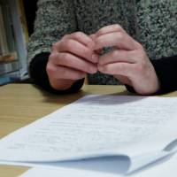 Hands of a woman from Fukushima Prefecture, who said her daughter was bullied at an elementary school, with documents related to the incident on March 4. | REUTERS