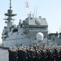 Maritime Self-Defense Force personnel line up on the newly commissioned Kaga helicopter carrier in Yokohama on Wednesday. | KYODO