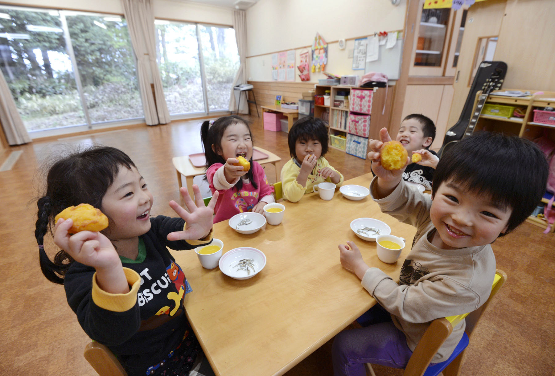 Children enjoy a snack at a nursery run by a private company in Noda, Chiba Prefecture. More Japanese firms are opening nurseries to meet a chronic shortage of day care services. | KYODO
