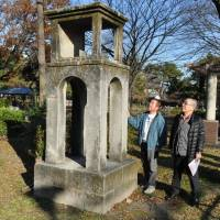 Shoshiro Ichihara (right), 77, looks up at an old radio tower in a park in Nagoya in this undated photo. | CHUNICHI SHIMBUN