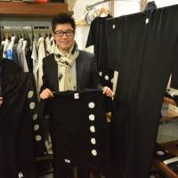 Tomoaki Nakamura (left) and his brother, Takehiro, show T-shirts and stoles made using the traditional dyeing method for black-crested kimono in Nagoya's Nishi Ward. | CHUNICHI SHIMBUN