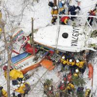 Officials examine a crashed helicopter Monday morning in a mountainous area in Nagano Prefecture. | KYODO