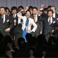 Democratic Party President Renho (center) and executives punch the air with their fists as party members watch during its annual convention held in Tokyo on Sunday. | KYODO