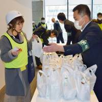 Participants receive a supply of emergency food at the Cabinet Office building during a disaster drill in central Tokyo on Monday. | KYODO