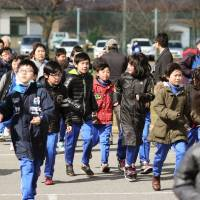 Elementary school students in Oga, Akita Prefecture, practice evacuating Friday, during a drill simulating a North Korean missile strike into nearby waters. | KYODO