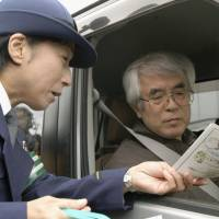 A police officer hands out a leaflet explaining the effects of age on driving in the city of Tachikawa, Tokyo, on Nov. 16. | KYODO