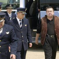 Kim Jong Nam is escorted by immigration officers to a Beijing-bound flight after being detained in May 2001 at Narita International Airport. | KYODO