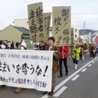 People march through the city of Fukushima in December to protest the impending end of housing subsidies for those who fled the nuclear disaster from areas other than the government-designated evacuation zones. | KYODO