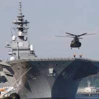 A helicopter lands on the Izumo, the Maritime Self-Defense Force's largest helicopter carrier, at Yokosuka, Kanagawa Prefecture, in December. | REUTERS