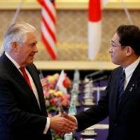 U.S. Secretary of State Rex Tillerson greets Foreign Minister Fumio Kishida on Thursday. Tillerson urged Japan to settle a diplomatic dispute with South Korea over so-called comfort women and focus on the North Korean threat. | REUTERS