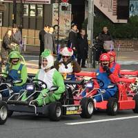 Tourists ride rented MariCar go-karts in Minato Ward, Tokyo, on Feb. 24. | MAGDALENA OSUMI