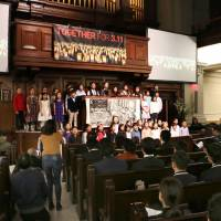 A choir performs a song for a memorial service Sunday at a church in New York to pray for the victims of the Great East Japan Earthquake of March 11, 2011. | KYODO