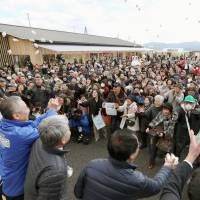 Visitors to the new shopping center in tsunami-hit Minamisanriku, Miyagi Prefecture, try to catch bags of rice cakes that were thrown to the crowd in celebration of its opening on Friday. | KYODO
