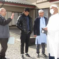 Sultan Mahmud (right), the head of the Chiba Mosque, and Yasuyuki Orinami (left), the chief of the security section at Chiba Kita Police Station, talk about community events in front of the mosque on Feb. 17. | KYODO