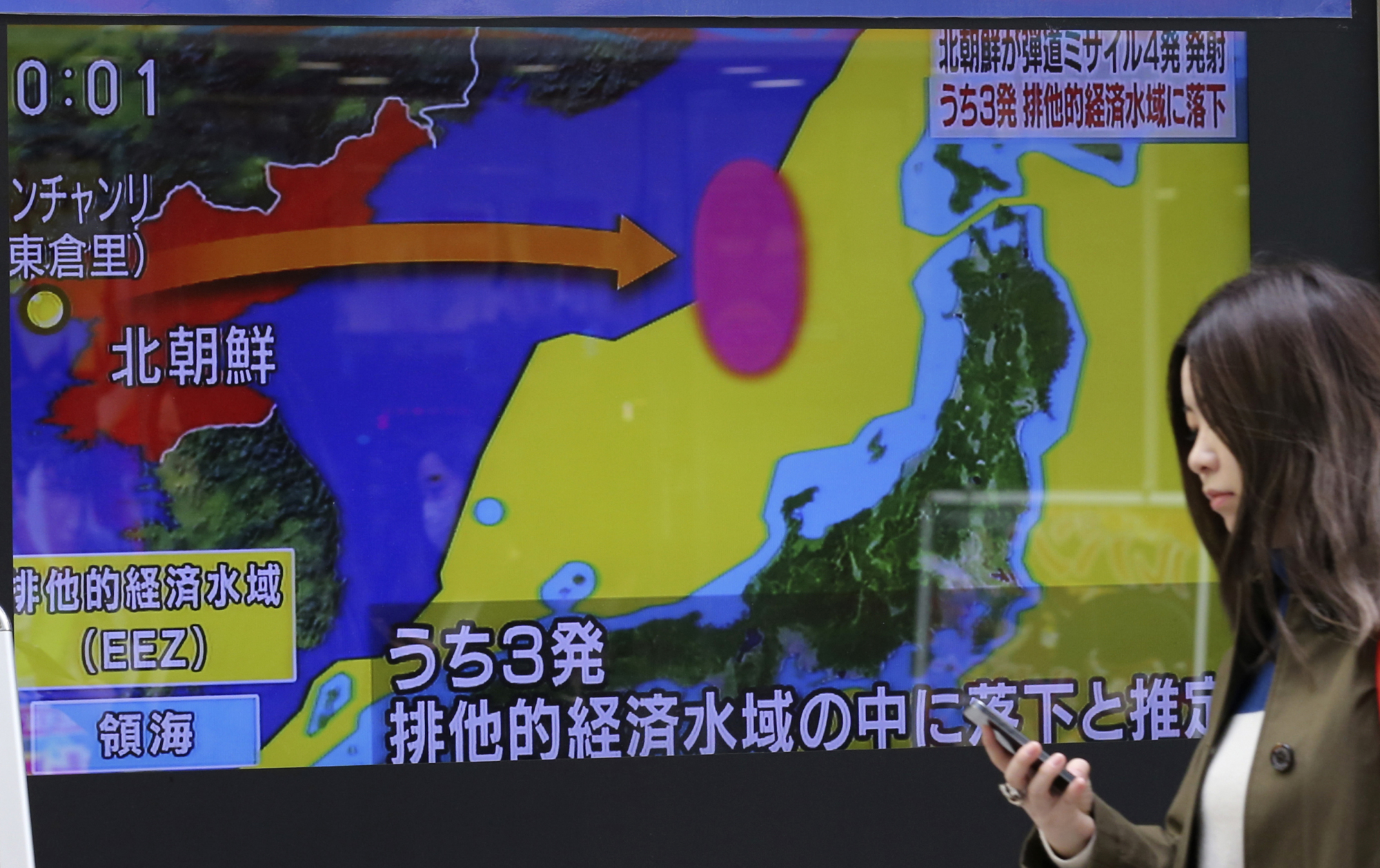 A woman walks past a screen showing a TV news program on a missile firing by North Korea with a map of Japan and North Korea in Tokyo on Monday. | AP