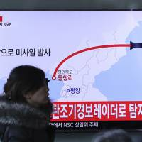 A woman walks in front of a TV screen at Seoul Train Station showing a news program reporting on North Korea's firing of four missiles Monday. | AP