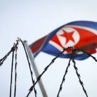 The North Korean flag is seen behind razor wire on top of a wall at the North Korean Embassy in Kuala Lumpurnon March 9. AP | AP