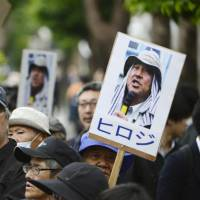 Protesters hold up placards showing photos of anti-base activist Hiroji Yamashiro, head of the Okinawa Peace Action Center, in front of the Naha District Court in Okinawa Prefecture on Friday. | KYODO