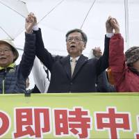 Okinawa Gov. Takeshi Onaga (center) takes part in a rally in Nago on Saturday to protest the relocation of a U.S. military base he wants removed from the prefecture. | KYODO