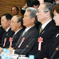 Keidanren chief Sadayuki Sakakibara (center) attends a meeting of a government panel on labor reform at the Prime Minister's Office on Tuesday. | KYODO