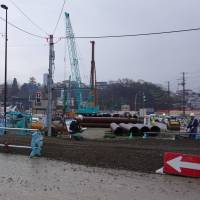 Construction continues in the fishing port of Kesennuma, Miyagi Prefecture, late last month. Six years after the 2011 quake-tsunami disaster, a planned full-fledged redevelopment project has yet to begin. | REIJI YOSHIDA