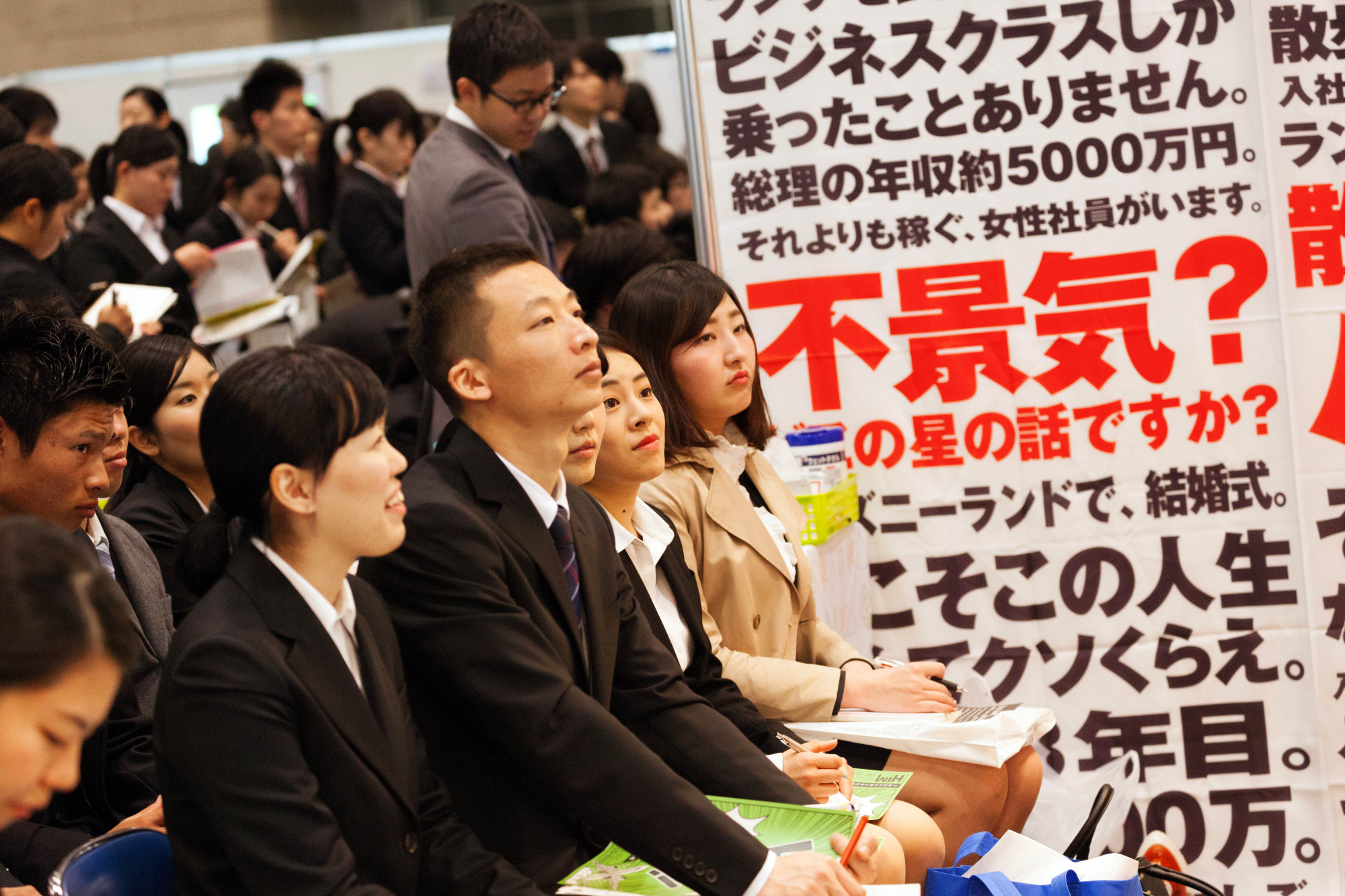 University students listen to a presentation as they attend a job fair at the Makuhari Messe convention center in Chiba Prefecture on March 1. | BLOOMBERG