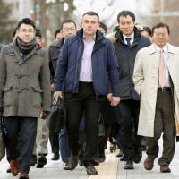 Andrei Novosyolov  walks with his lawyers to the Sapporo District Court on Tuesday to attend the retrial of his 1997 handgun possession case. | KYODO