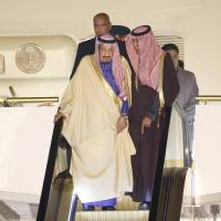 Saudi Arabian King Salman bin Abdul-Aziz (left) rides on a special escalator as he disembarks from his plane following its arrival at Haneda airport in Tokyo on Sunday evening. Salman's visit to Japan is part of the monarch's month-long tour of Asia. | AP