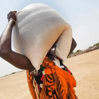A woman carries a sack of food aid in Ganyiel, South Sudan on March 4. | AFP-JIJI