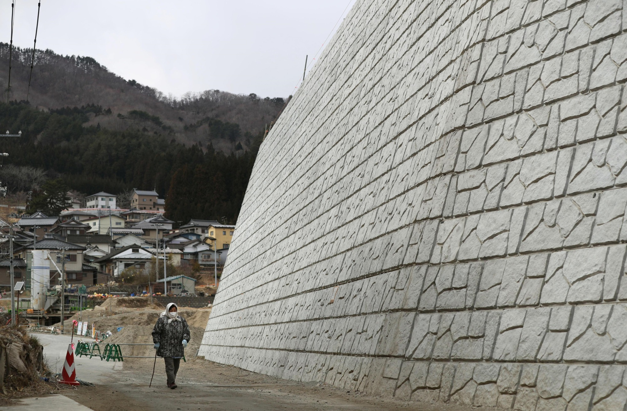 A woman walks along a 14.5-meter-high seawall being built in Kamaishi, Iwate Prefecture, on Thursday. | KYODO