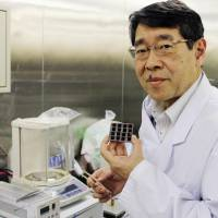 Tsutomu Miyasaka holds a solar cell with perovskite crystals painted on it at Toin University of Yokohama in March 2015. | KYODO