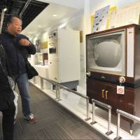 Visitors check out a display about Toshiba's first color TV at the Toshiba Science Museum in Kawasaki on March 8. | YOSHIAKI MIURA