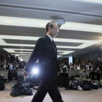 Toshiba Corp. President Satoshi Tsunakawa arrives for a news conference in Tokyo on Tuesday. Toshiba is considering selling a majority stake in its Westinghouse nuclear unit. | BLOOMBERG