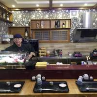 Japanese sushi chef Kenji Fujimoto works behind the counter of his new restaurant in Pyongyang on Feb. 19. | AP