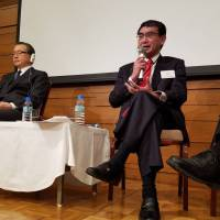 Lawmakers Kono Taro (right) and Masaharu Nakagawa (center) stress the importance of Japan opening its doors to blue-collar foreign workers at a symposium in Tokyo on Feb. 22. | TOMOHIRO OSAKI