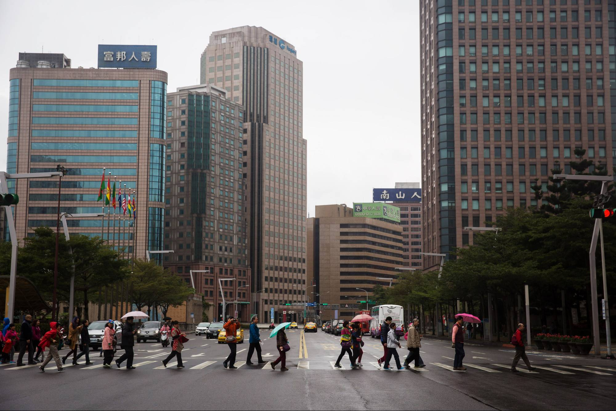 Pedestrians holding umbrellas cross a road near commercial buildings in Taipei in January, 2016. | BLOOMBERG
