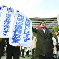 Plaintiffs hold banners in front of the Osaka High Court on Tuesday expressing disappointment after the court ruled in favor Kansai Electric over the restart of two Takahama reactors. | KYODO