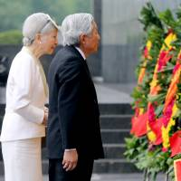 Emperor Akihito and Empress Michiko attend a wreath-laying ceremony at the mausoleum of late Vietnamese President Ho Chi Minh in Hanoi on Wednesday. | REUTERS