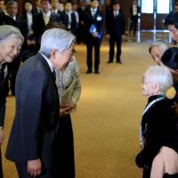 Nguyen Thi Xuan (right), 93, who married a former Japanese soldier, greets Japan's Emperor Akihito and Empress Michiko as they meet at a hotel in Hanoi with family members of Japanese veterans living in Vietnam on Thursday. | AFP-JIJI